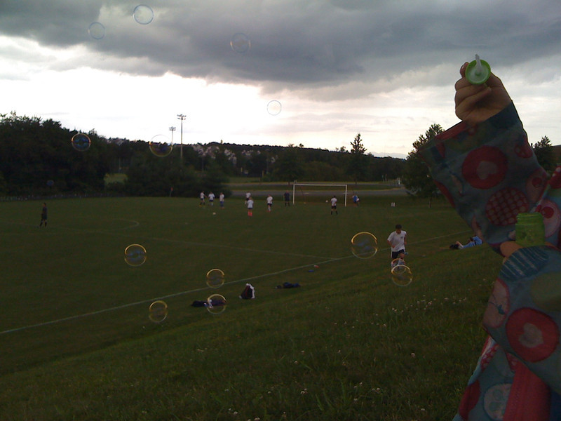 Sam blows bubbles at AC's soccer game